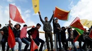 Turkish Kurds wave flags with the lettering 'No' in Turkish and Kurdish as they gather for Newroz celebrations for the new year in Diyarbakir, southeastern Turkey, on March 21, 2017.