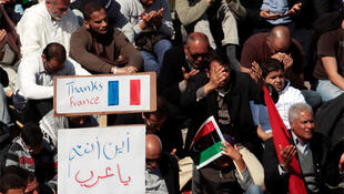 Protesters sit near a sign with a French flag drawn on it in Benghazi, 11 March.