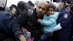 Cet homme portant une fillette dans les bras lutte pour passer le cordon policier avant la frontière gréco-macédonienne, ce vendredi 4 décembre 2015 près du village d'Idomeni.