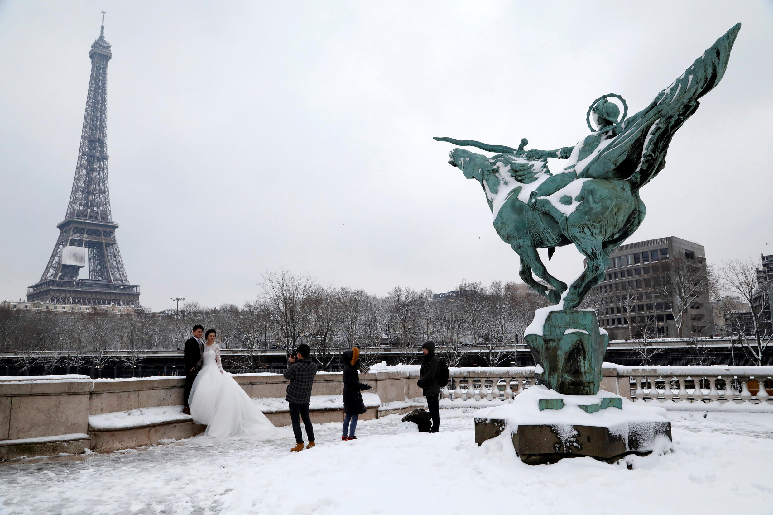 Newly weds pose in the snow in front of the Eiffel Tower