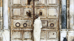 Un peregrino cristiano ataviado como Jesucristo se detiene ante la puerta cerrada de la iglesia del Santo Sepulcro, el 10 de abril de 2020 (Viernes Santo) en la Ciudad Vieja de Jerusalén