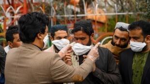 فردی در هرات واقع در غرب افغانستان و مرز ایران داوطلبانه میان شماری از شهروندان ماسک توزیع میکند - ٢٦ فوریه ٢٠٢٠