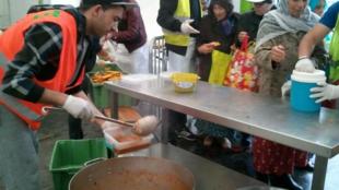 Volunteers serving takeaway chorba during ramadan