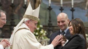 Le pape François baptisant un des 32 bébés durant une messe dans la chapelle Sixtine, au Vatican, le 12 janvier 2014.