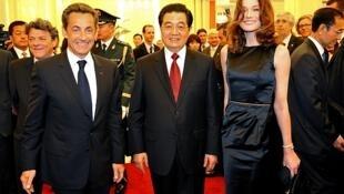 El presidente de China, Hu Jintao, da la bienvenida al presidente francés Nicolas Sarkozy y a su mujer, Carla Bruni Sarkozy.