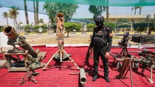 Un membre des forces d'opérations spéciales d'Irak se tient près d'armes saisies dans d'anciennes positions de l'organisation terroriste État islamique, près de Bagdad, le 6 août 2019. (Illustration)