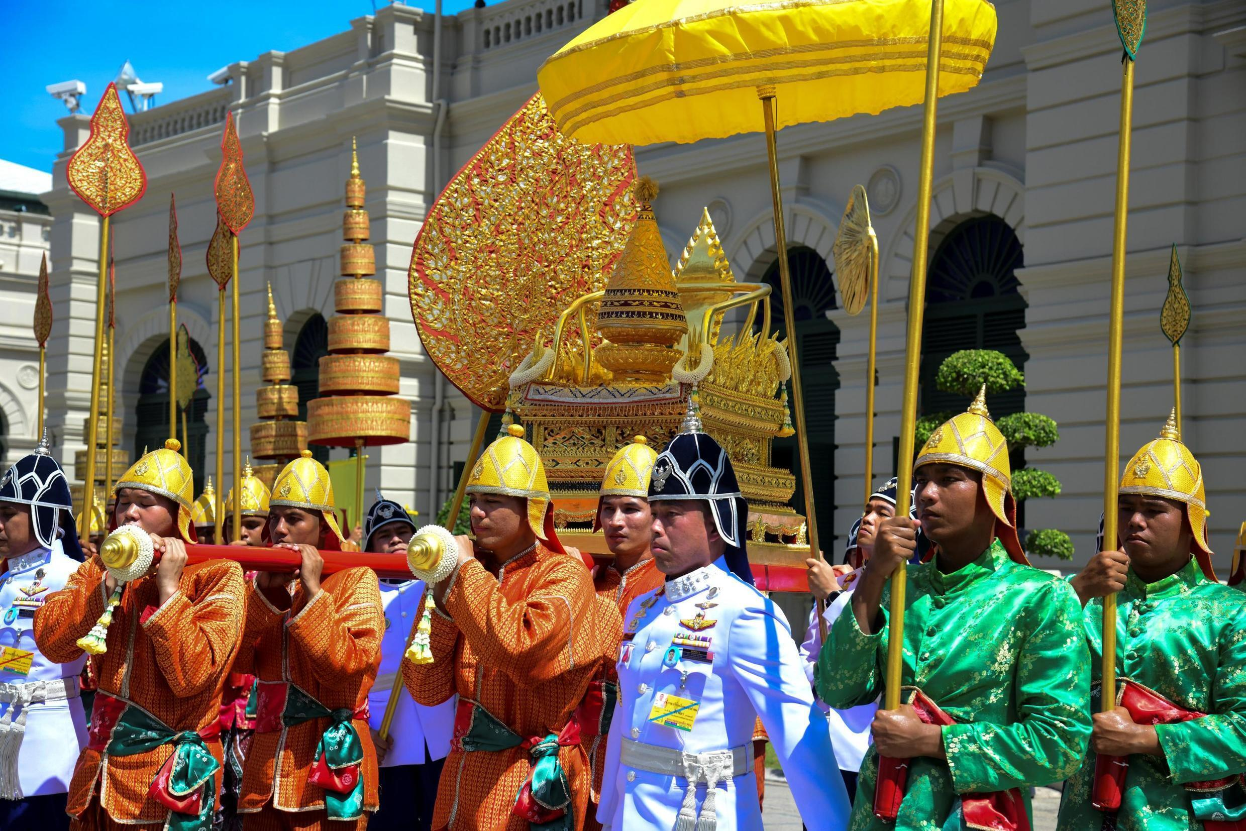 Thai soldiers dressed in traditional costumes transfer The Royal Golden Plaque of the official title of His Majesty the King, the Royal Golden Plaque of His Majesty's horoscope, and the Royal Seal of State at the Grand Palace in Bangkok