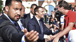French President Emmanuel Macron (C), flanked by Elysee senior security officer Alexandre Benalla (L), shakes hands with people after he voting in Le Touquet, northern France, during the second round of the French parliamentary elections.