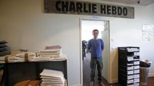 """Mchoraji Vibonzo Charb, mhariri wa jarida la vibonzo la """"Charlie Hebdo"""" katika makao makuu ya jarida hilo, mwezi  Septemba mwak 2012."""