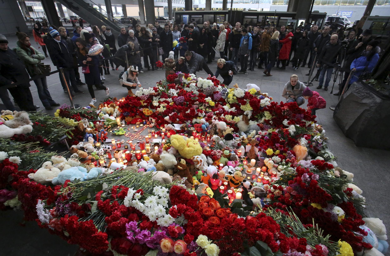 Flores e velas no aeroporto de Poulkovo, onde aterrissou o avião com os corpos das vítimas