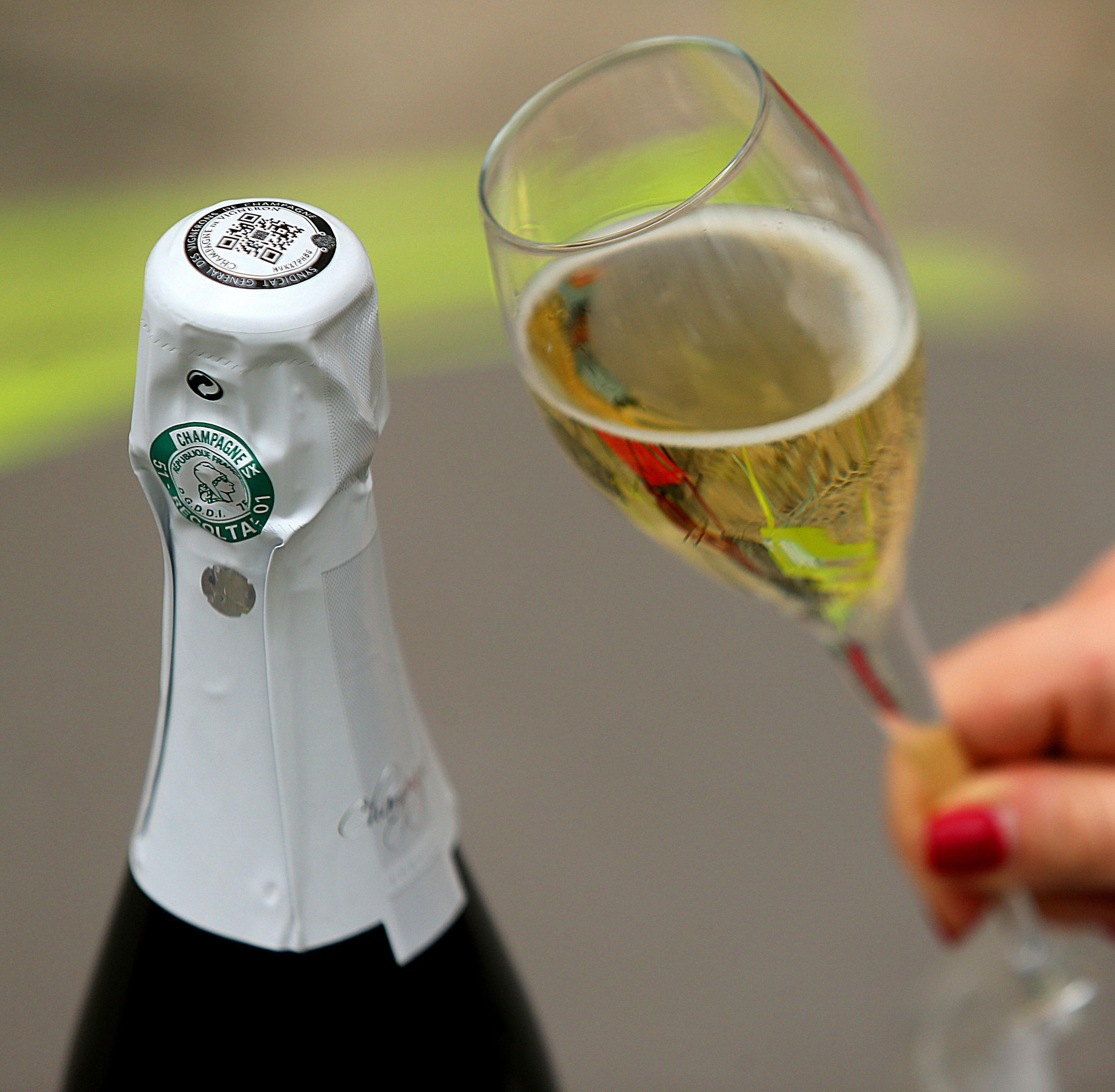 (FILES) A file photo taken on May 6, 2019 shows a glass of champagne next to a bottle which label contains a QR code to guarantee its traceability in Epernay, eastern France, at the General Syndicate of Winegrowers of Champagne (SGV).Champagne sales fell of 18% in 2020 as a consequence of the Covid-19 epidemic. According to the Champagne Committee, which brings together producers and traders, 245 million bottles were sold worldwide during the year due to the closure of hotels, bars and restaurants and the decline in tourism in France in particular, indicated the organisation on January 26, 2021.