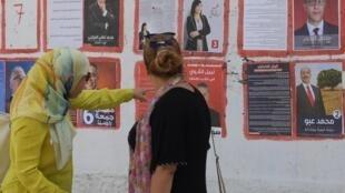 Des Tunisiennes passent devant des affiches électorales le 9 septembre 2019, quelques jours avant l'élection présidentielle qui doit se tenir le 15 septembre 2019.
