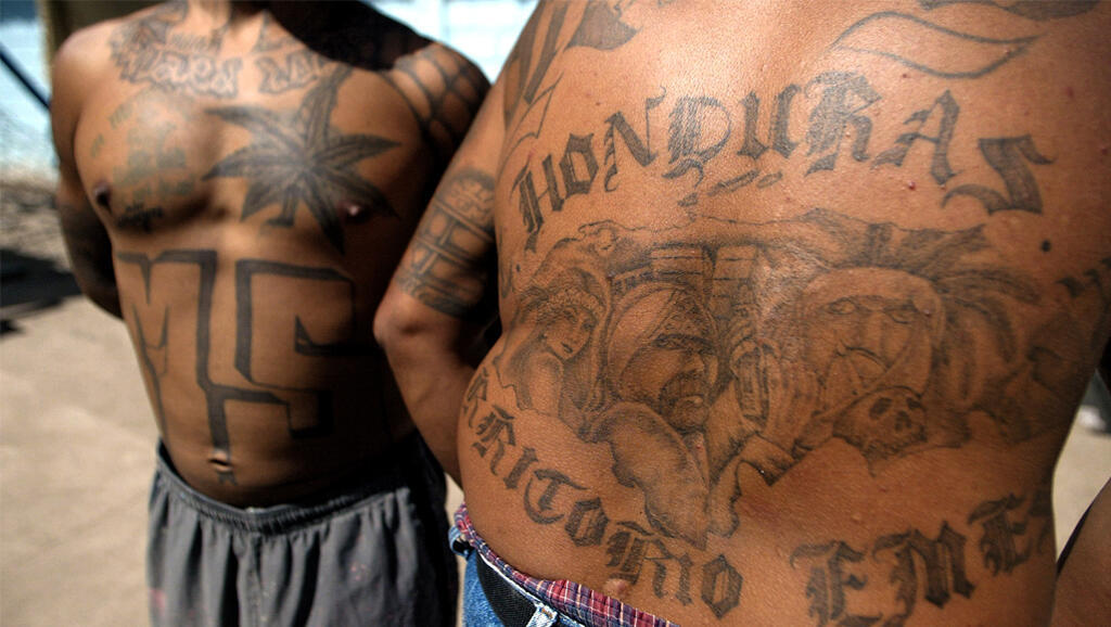 """Deux membres du gang """"MS-13"""" exhibent leurs tatouages, à la Prison de Tamara (Honduras). Photo datée de février 2006."""