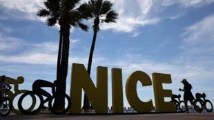 Une femme passe devant le logo du départ du Tour de France 2020 sur la promenade des Anglais à Nice, le 26 août