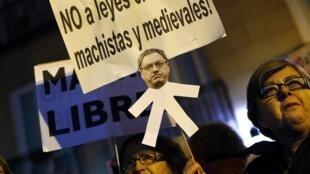 «Non aux lois religieuses, sexistes et médiévales», indique le panonceau de cette manifestante à Madrid, le 20 décembre.