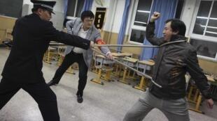 警員在北京一學校示範鋼叉的效用,該校老師(右)扮演襲擊者被叉住
