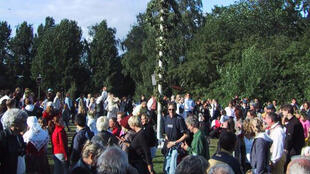 """Des Suédois de tous âges célèbrent  le """"mât fleuri de la Saint-Jean""""."""