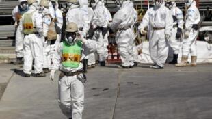 Funcionários da Tepco trabalham ao lado do reator n°4 de Fukushima, em Fukushima, em foto de arquivo.