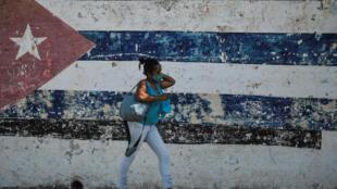 Una mujer camina en La Habana junto a un muro donde está pintada la bandera de Cuba, el 22 de junio de 2021