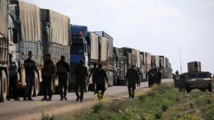 Membros das Forças Democráticas sírias (FDS) caminham ao lado dos camiões que deixam Al - Baghuz com civis no seu interior, a 20 de Fevereiro de 2019