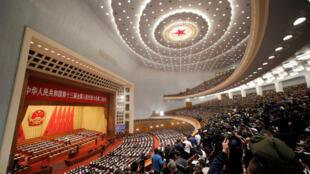 Des délégués et des journalistes assistent à l'Assemblée nationale populaire (APN) au Grand Palais du Peuple à Beijing, le 5 mars 2019.