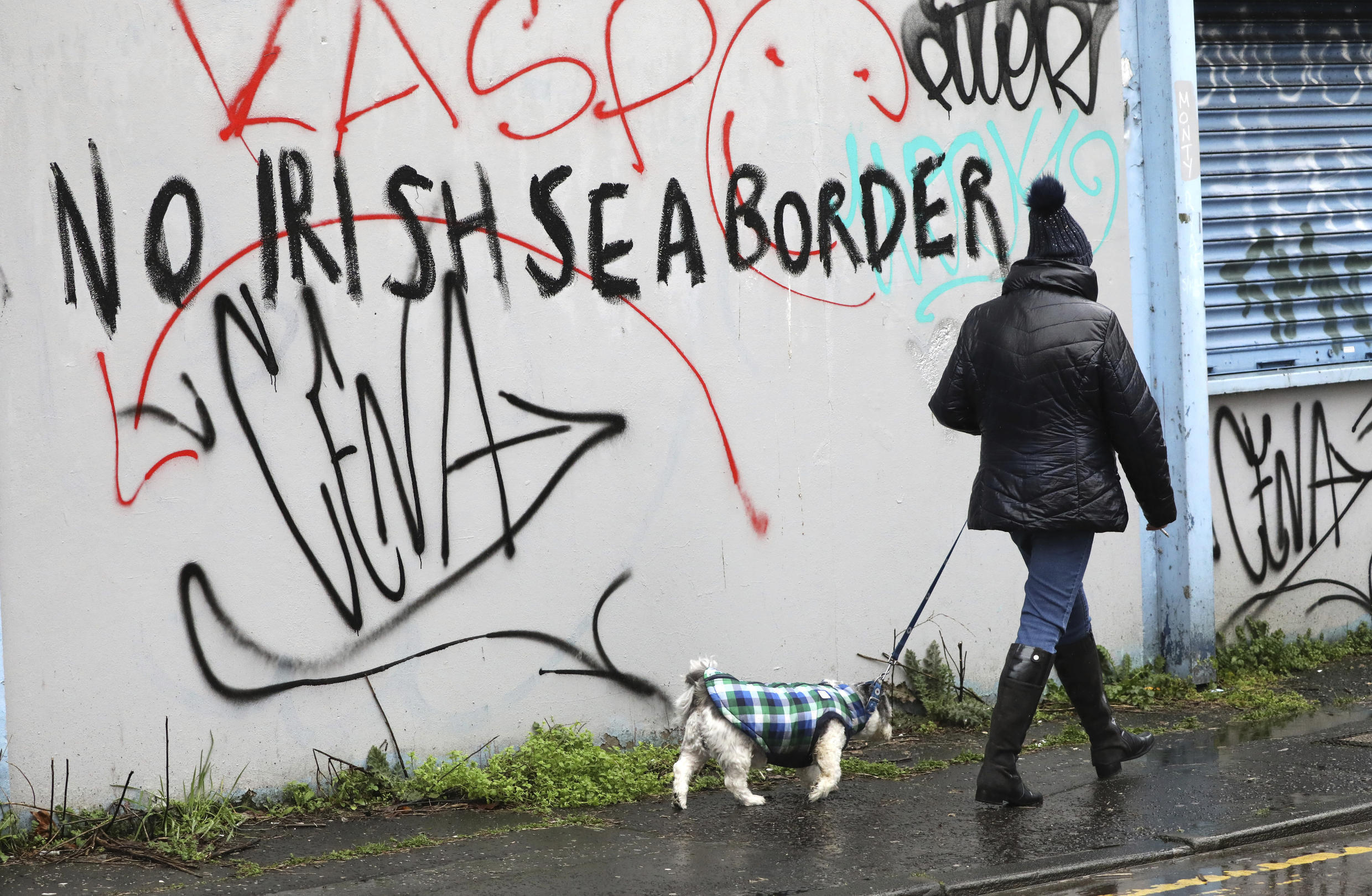 A woman walks her dog past past graffiti with the words 'No Irish Sea Border' in Belfast city centre, Northern Ireland, Wednesday, Feb. 3, 2021. Politicians from Britain, Northern Ireland and the European Union are meeting to defuse post-Brexit trade tensions that have shaken Northern Ireland's delicate political balance. British Cabinet minister Michael Gove, European Commission Vice President Maros Sefcovic and the leaders of Northern Ireland's Catholic-Protestant power-sharing government will hold a video conference to discuss problems that have erupted barely a month after the U.K. made an economic split from the 27-nation EU.