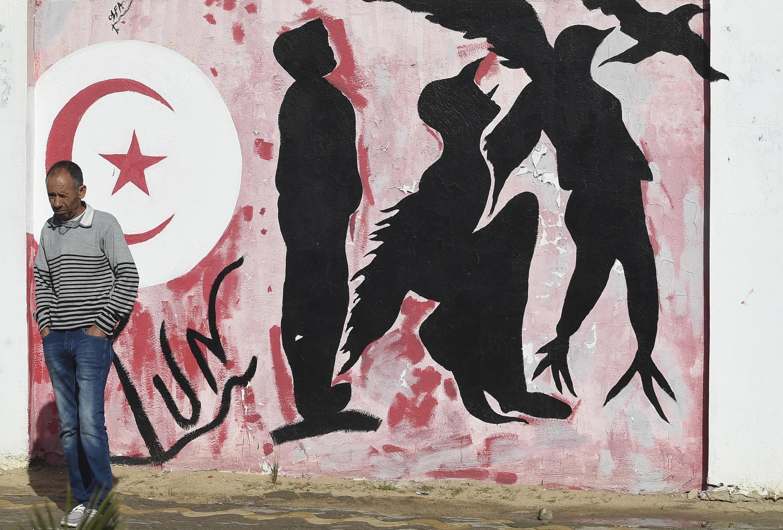 Un hombre delante de un grafiti en la plaza Mohamed Bouazizi, en el centro de Sidi Bouzid, el 27 de octubre de 2020
