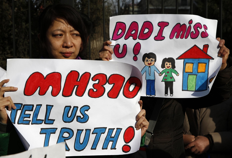 """Женщина, муж которой был на борту исчезнувшего """"Боинга"""" держит плакат """"МН370 - Скажите нам правду"""" на собрании семей жертв авиакатастрофы, 8 марта 2015 г."""