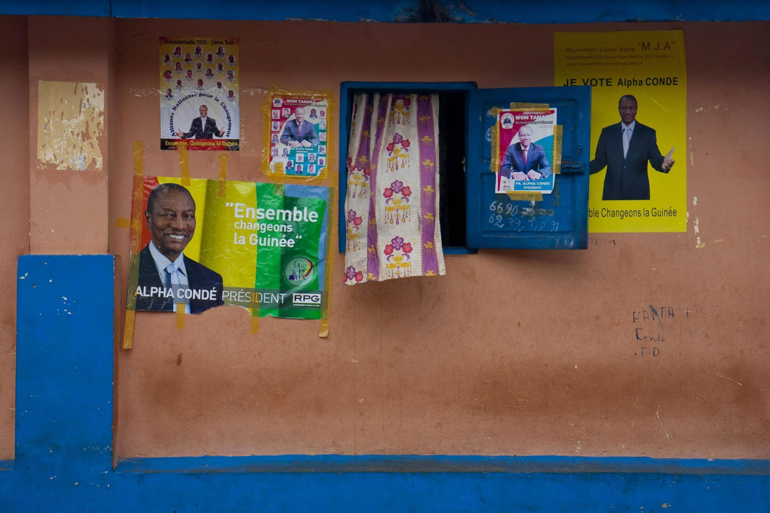 Posters for Guinea's presidential candidates outside a home in downtown Conakry, the capital