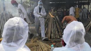 Allegados de personas fallecidas por covid-19 realizan los últimos ritos funerarios en un crematorio de Ghazipur (India) el 1 de mayo de 2021