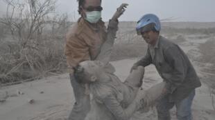 Moradores de Sukameriah, na ilha de Sumatra, Indonésia, socorrem homem atingido pela erupção do vulcão Sinabung.