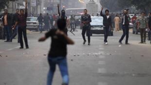 Manifestante anti-Morsi joga pedras em apoiadores do presidente deposto na Praça Tahir, no Cairo, nesta segunda-feira, 2 de dezembro de 2013.
