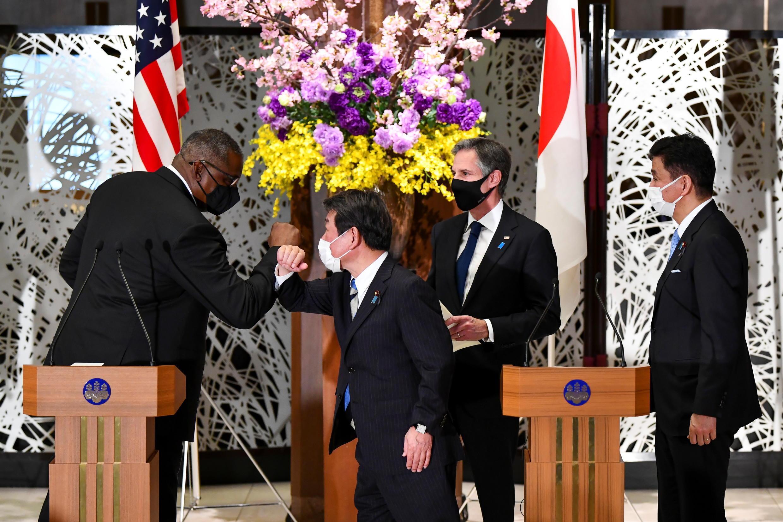 Bộ trưởng Quốc Phòng Mỹ Lloyd Austin (T) và ngoại trưởng Nhật Toshimitsu Motegi chạm khủyu tay chào nhau trước khi các bộ trưởng họp báo chung, tại Tokyo, Nhật Bản, ngày 16/03/2021.
