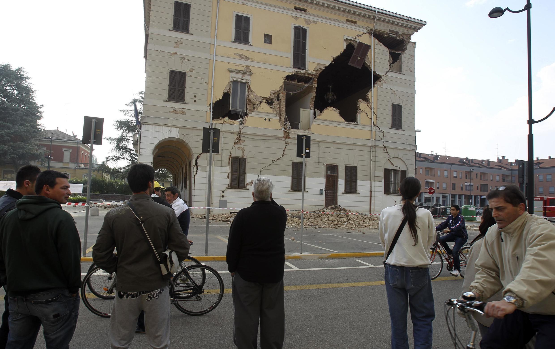 Moradores de Santo Agostinho, próximo a Ferrara, observam danos na parede da prefeitura local.