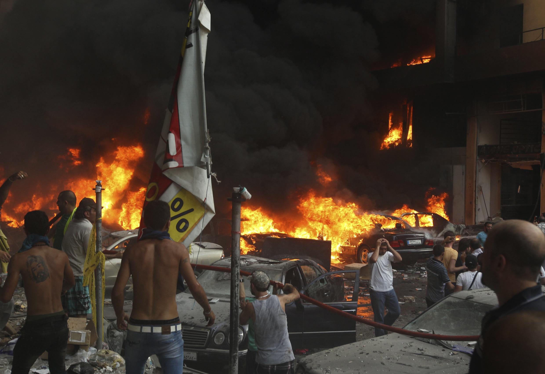 Moradores tentam apagar o incêndio provocado pela explosão do carro-bomba na periferia de Beirute.