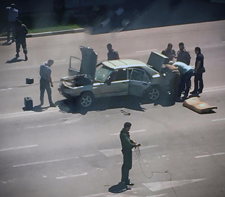Photo du Comité d'enquête russe montrant des policiers tchétchènes en train de fouiller la voiture utilisée par un assaillant à Grozny, le 20 août 2018.