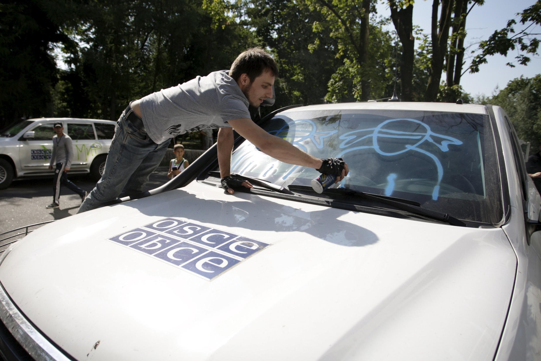 Демонстрант рисует граффити на автомобиле Специальной мониторинговой миссии ОБСЕ в Донецке во время протестной акции, 23 июля 2015 г.