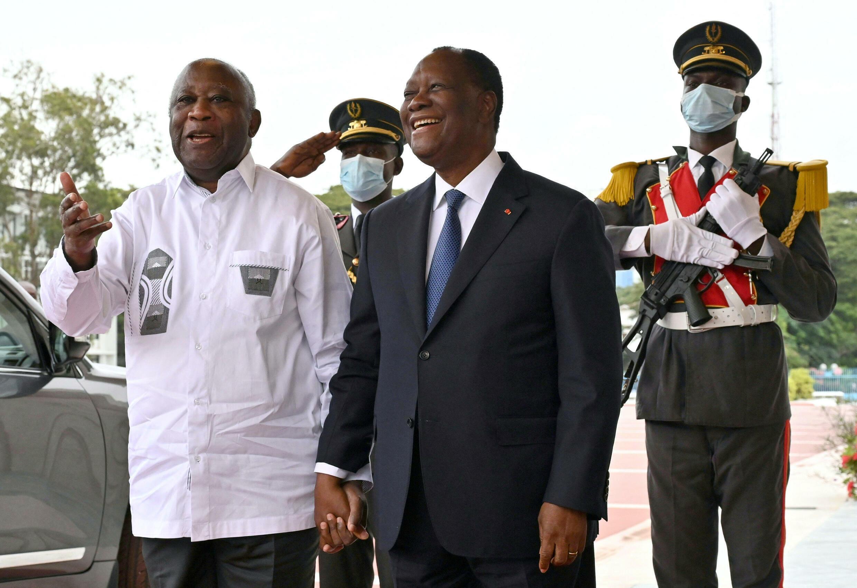 O Presidente  Alassane Ouattara de mãos dadas com o seu antecessor, Laurent Gbabgo no palácio presidencial de Abidjan, a 27 de Julho de 2021, durante o seu primeiro encontro desde Novembro de 2010.