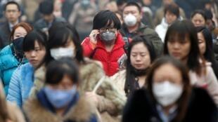 中國北京罩陰霾的早晨上班族戴口2014年2月26日。