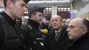 Le ministre de la Défense Jean-Yves Le Drian (second à droite) et le ministre de l'Intérieur Bernard Cazeneuve (D) à la gare de Lyon lors de leur tournée d'inspection du plan Vigipirate. Paris, le 16 janvier 2015.