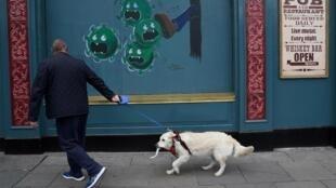 Un passant dans les rues de Dublin, devant un tag illustrant la crise du coronavirus.