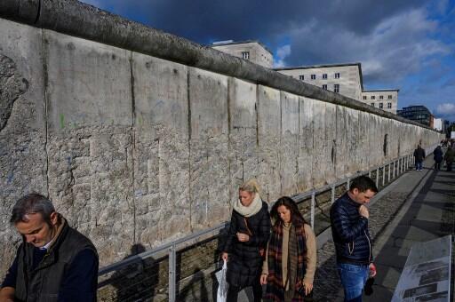 Des touristes longent ce qui reste du mur de Berlin, conservé pour l'histoire.