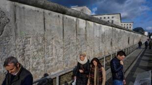 Des touristes longent ce qui reste du Mur de Berlin.