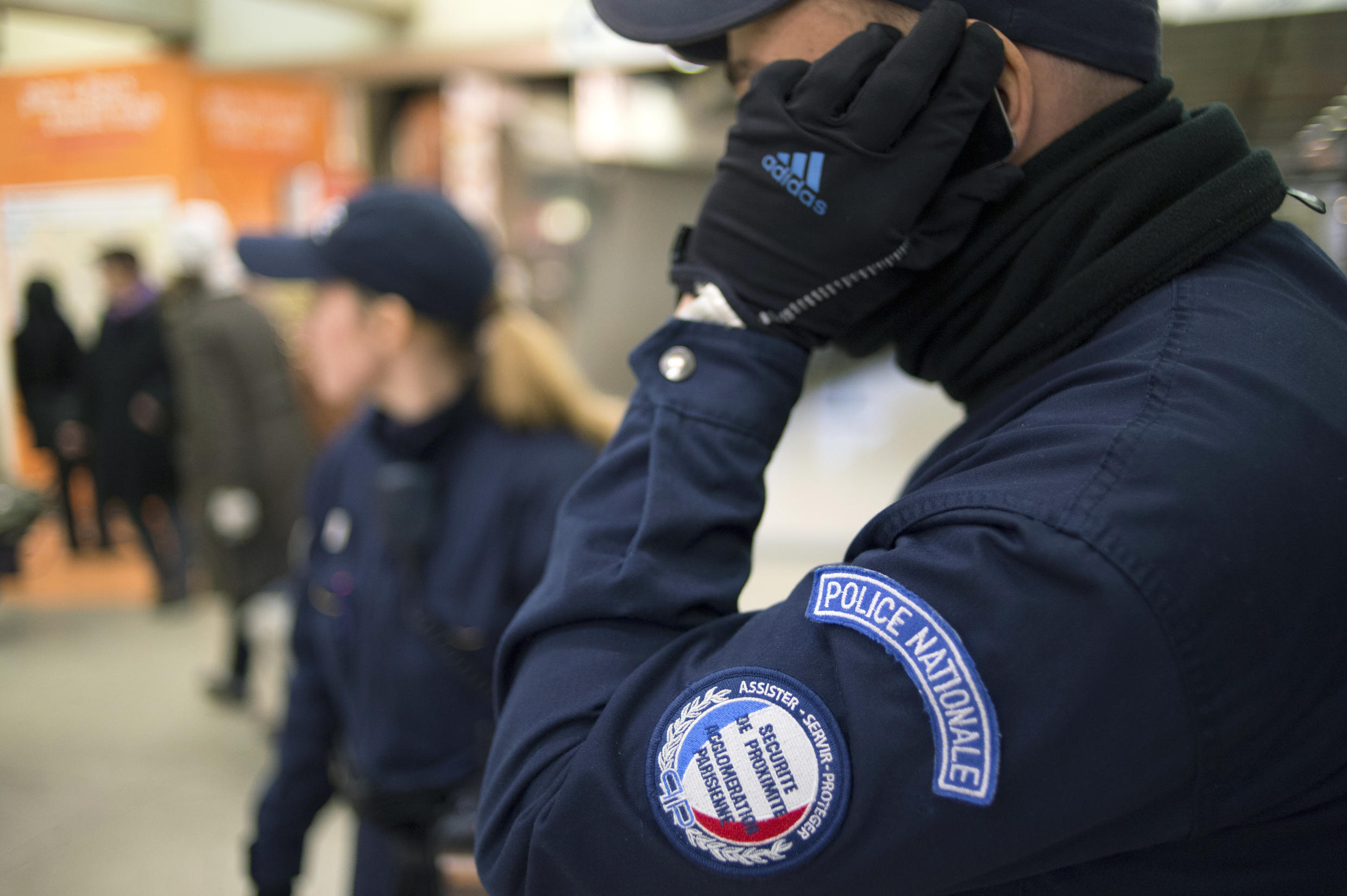 A policeman talks on a cell phone during a patrol of the Gare du Nord  in Paris on November 29, 2012