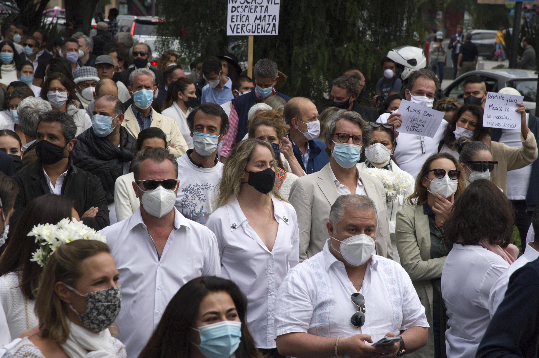 La gente participa en una marcha organizada por la comunidad francesa en México pidiendo la aclaración de la muerte del empresario francés Baptiste Lormand, el 30 de noviembre de 2020 en Ciudad de México