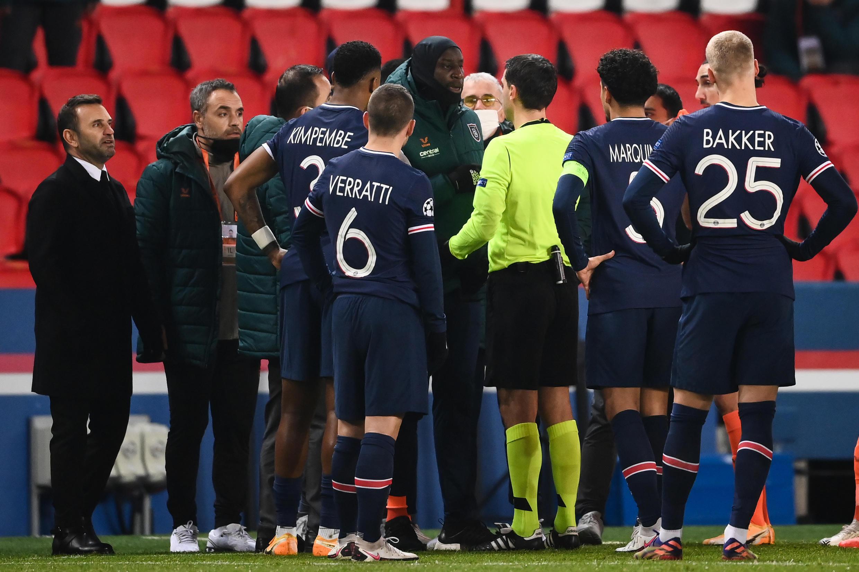 L'attaquant d'Istanbul Basaksehir Demba Ba (au centre) en discussion avec l'arbitre du match PSG-Basaksehir à Paris après une interruption en raison de propos supposés racistes du 4e arbitre, le 8 décembre 2020