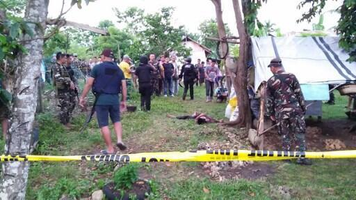 Philippine soldiers standing next to a dead body of one of the two Abu Sayyaf militants killed in an encounter with troops in Calape town, Bohol province, central Philippines.