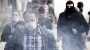 Manifestantes correm em ponte que leva à praça Tahir no Cairo (Egito) em protesto no domingo 27 de janeiro de 2013.