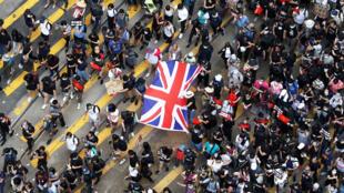 Собравшиеся возле дипмиссии пели британский гимн, вруках некоторых были плакаты сослоганами«Совместная декларация—путышка»и«SOS Гонконг».