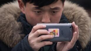 Un Nord-Coréen prend une photo avec son smartphone à Pyongyang.